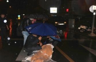 Motosikletten Düşen Kadını Yağmurdan Korudular